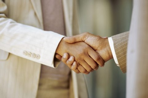 close-up of a businessman shaking hands with a businesswoman